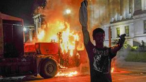 En man med höjd näve står framför en brinnande lastbil