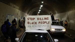 """Demonstranter står i en tunnel. Två vita bilar syns på bilden över den bilens tak håller en demonstrant ett plaket med texten """"Stop killing black people""""."""