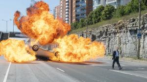 En man står framfölr en bil som exploderat i ett enorms moln av eld.