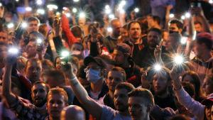 En stor grupp människor håller upp sina mobiltelefoner