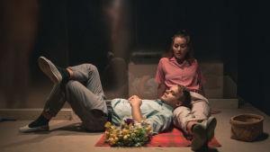 En man ligger på golvet med huvudet i en kvinnas knä.