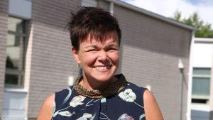 En leende kvinna med kort mörkt hår kisar. I bakgrunden syns en grå tegelbyggnad.
