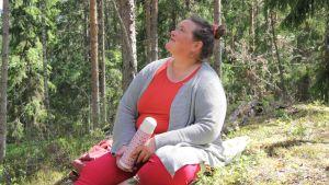 psykologi Liisa Uusitalo-Arola metsäretkellä nauttii eväitä iloisena