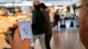 En person har en mobil i handen och appen Coronablinkern är öppen och visas på skärmen. Bakgrunden med några människor och ljus är suddig.