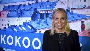 porträttbild av Elina Lepomäki framför storbild med hustak och en del av Samlingspartiets logo