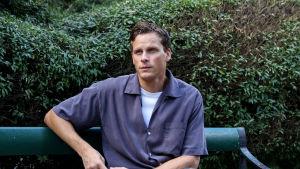 Adam Pålsson sitter på en bänk i ett grönområde. Han tittar snett framåt, ena armen lutar mot bänken och andra har han i knäet.