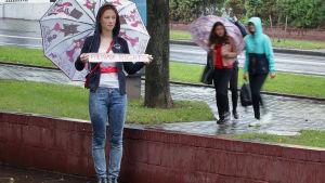 """En ung kvinna håller upp en lapp med texten """"For Human Rights""""."""