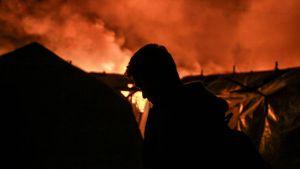 En man står framför brinnande byggnader