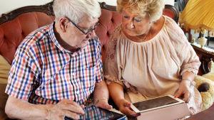 Seniorit somessa -sarjassa tavatut Pentti Heinonen ja Lea Musone käyttävät tablettitietokoneita.