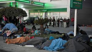Hemlösa migranter och flyktingar sover marken vid en bensinstation på Lesbos