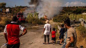 Migranter tittar på eldar som tänts i samband med lördagens protester.