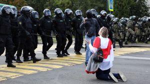 En kvinna knäböjde inför kravallpolisen under söndagens demonstration.