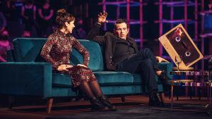 Timo Lavikainen selittää tarinaa sohvalla, vieressä Elena Leeve.