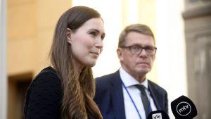 Statsminister Sanna Marin och finansminister Matti Vanhanen står bredvid varandra på Ständerhusets trappa och svarar på journalisternas frågor i mikrofoner.