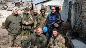 Antti Kuronen poserar med lokala män i kamouflagekläder i Ukraina med tv-kamera i handen.