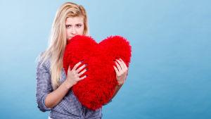 Sorgsen blond kvinna med röd hjärtformad kudde i famnen