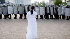 Kvinna som ställer sig emot polisen under en demonstration i Minsk