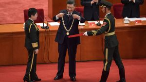Kinas president Xi Jinping belönar en kinesisk general som lett ett vaccinforskningsteam. 8.9.2020