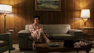 På bilden syns skådespelaren Sarah Paulson i rollen som Mildred Ratched. Hon är iklädd 1950-tals kläder och sitter på en soffa ensam i ett rum.