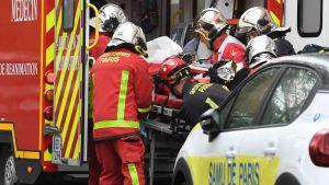 Räddningspersonal lyfter en en sjukhusbår i ambulansen i Paris.