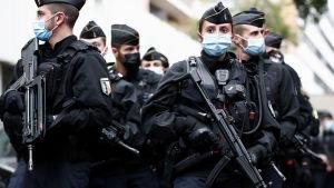 Flera poliser med automatvapen stor i en klunga