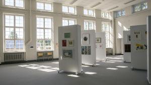 Utställningslokal med  färggrann bildkonst på vita upphängningsblock, stora ljusa fönster.