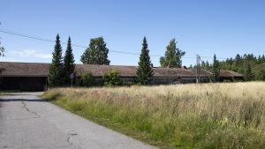 Ängar och en låg röd byggnad.