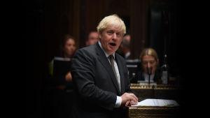 Boris Johnson står vid ett förgyllt bord och talar.