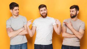 Tre unga män i ljus t-skjortor, den i mitten ler självsäkert medan de andra tittar surt på honom