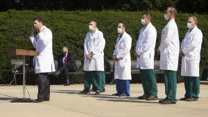 En läkare i vit rock håller presskonferens. I bakgrunden står flera andra personer i vita rockar