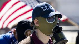 En person iförd gas mark. I bakgrunden syns USA:s flagga.