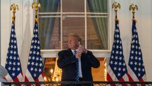 Donald Trump står på Vita husets trappa framför amerikanska flaggor och tar av sig sitt munskydd när han kommer hem från sjukhuset.