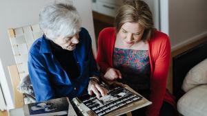 Märta Tikkanen och Johanna Holmström tittar på gamla fotografier.