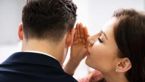 En kvinna som viskar en mans öra.