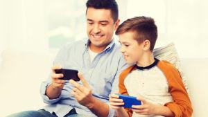 man och pojke sitter i soffa och tittar på smarttelefoner