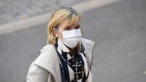 Kvinna med ljust hår och munskydd ser in i kameran. Kvinnan är justitieminister Anna-Maja Henriksson.