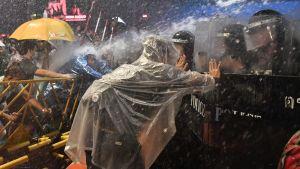 Person iförd i regnrock som trycker mot polisens kravallsköld.