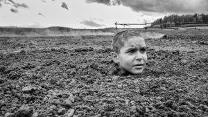 Den lilla pojken Joska upp till halsen begravd i lera.