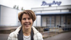 Leende kvinna står framför fabriksbyggnad. På en suddig skylt i bakgrunden står det Brunberg.