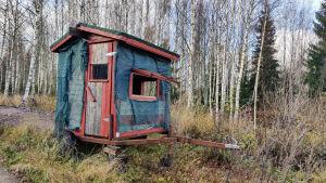 En litet blått hus på en släpvagn med hjul.