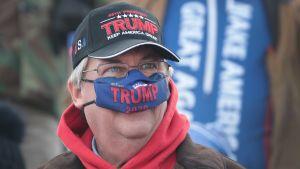 Manlig Trump-anhängare med coronaskydd över näsan.