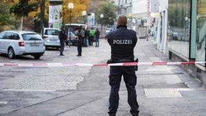En polis står med ryggen vänd mot kameran invid ett avspärrningsband i centrala Wien.