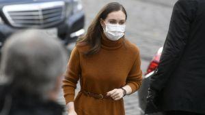 Sanna Marin i munksydd och brun kappa utanför Ständerhuset.