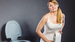Bekymrad kvinna med toalettpappersrulle i handen