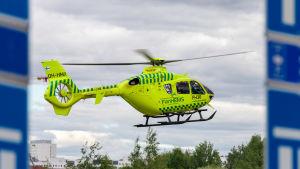 FinnHEMS neongula helikopter flyger.