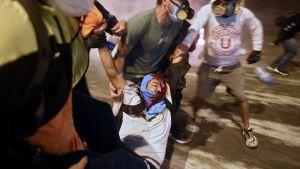 En demonstrant som stöder president Martin Vizcarra får hjälp efter att ha skadats av kravallpolis under en demonstration mot interimspresidenten Manuel Merino 14.11.2020