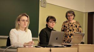 Två flickor sitter framför var sin dator. Bredvid ena flickan står en kvinna.