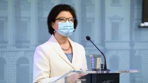 Liisa-Maria Voipio-Pulkki  i munskydd på presskonferensen.