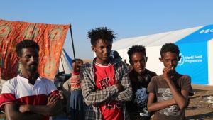 Fyra män och pojkar står framför ett tält