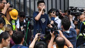 Demokratiaktivisten Joshua Wong talar till demonstranter utanför polishögkvarteret i Hongkong 21.6.2020